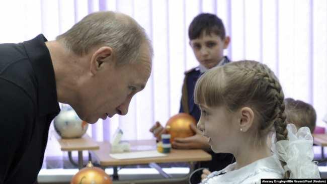 Владимир Путин в бытность премьер-министром России беседует со школьницей во время посещения сельской школы в Хакасии. Село Черемушки, 19 декабря 2011 года.