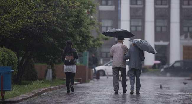 Горожане идут по улице во время дождя. Архивное фото